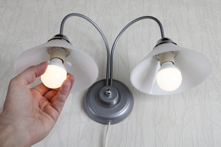 Make The Switch To Energy-Efficient LED lamp, Hand Replacing electric light bulb