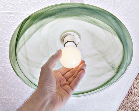 Replacing the electric light bulb in the Ceiling luminaire, close-up of a human hand twists LED lamp low power consumption in the shade of frosted glass.