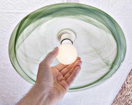 Remplacement de l'ampoule électrique dans le luminaire au plafond, close-up d'un torsions humain main lampe LED à faible consommation d'énergie à l'ombre de verre dépoli. Banque d'images
