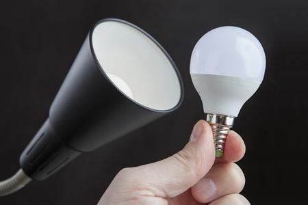 bombilla LED de luz eléctrica en la mano del hombre cerca de la pantalla de una lámpara de pie, contra un fondo oscuro. Foto de archivo
