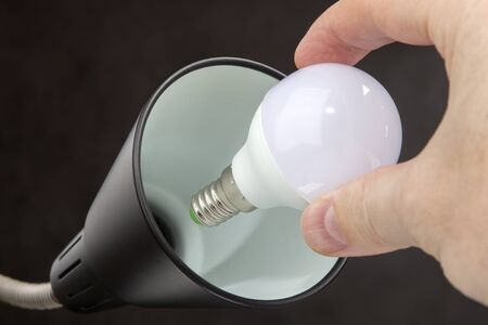 led lighting: Hand holds a LED lamp low power consumption, the replacement of light bulbs in a floor lamp, black background.