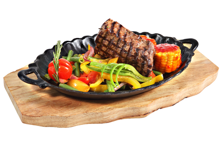 serving dish: Mexican steak in cast-iron oval serving dish with handles on a wooden plate, isolated on white background. Stock Photo