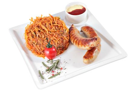 chorizos asados: Salchichas a la parrilla con guarnición de col estofado y salsa en el plato de servir cuadrada, aislado sobre fondo blanco.