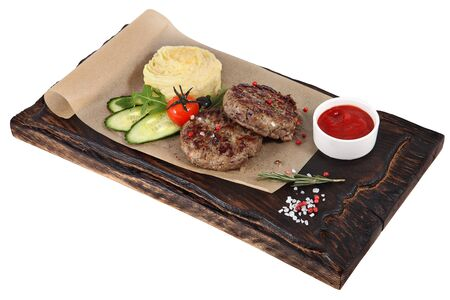 vealy: Two veal cutlets with garnish on dark brown serving board, isolated on white background. Stock Photo