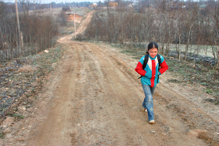 roadless: Lipovec village, Tver region, Russia - May 3, 2006: One Russian rural schoolgirl Tanya 11 years old goes to school early in morning, in spring, in cold weather, along a country road in countryside Editorial
