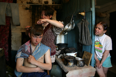 kindred: Lipovec village, Tver region, Russia - May 7, 2006: Family Russian farmers in his home, Mother makes her son hairstyle, rural house.