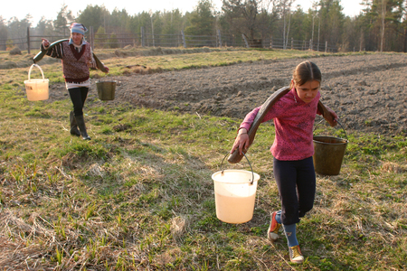 agriculturalist: Lipovec village; Tver region; Russia - May 2; 2006: Russian Farmer girl Carrying Water Buckets