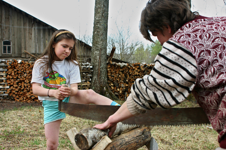agriculturalist: Lipovec village, Tver region, Russia - May 6, 2006: Russian peasants, villagers mother and daughter sawn dry timber for firewood, using two-handed saw. Editorial