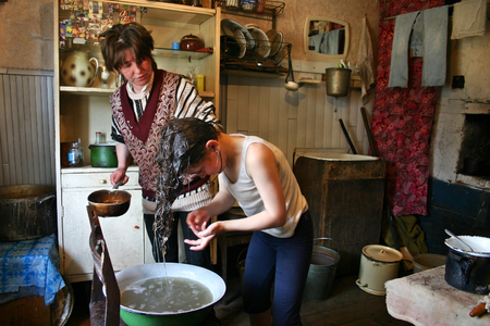 11 years: Lipovec village, Tver region, Russia - May 6, 2006: Girl Tanya 11 years old washes his head in an enamel basin, standing in the kitchen of the farmhouse, her mother standing next to a ladle in hand. Editorial