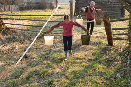 agriculturalist: Lipovec village, Tver region, Russia - May 2, 2006: Girl carrying two heavy pails filled with water suspended from a shoulder yoke on her  farm.