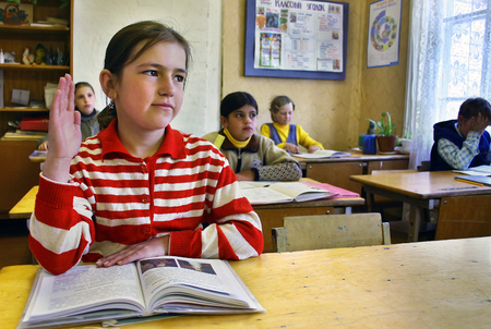 Podol village, Tver region, Russia - May 7, 2006: Rural girl schoolgirl Tanya 11 years old raises his hand, sitting at the desk in the classroom.