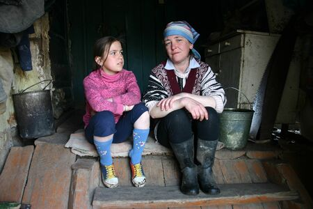 countrified: Lipovec village, Tver region, Russia - May 2, 2006: Peasant women are sitting on the steps of the entrance to the rural home. Editorial