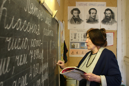 schoolmaster: Podol village, Tver region, Russia - May 5, 2006: School teacher writes with chalk on the blackboard in the classroom of rural school. Editorial