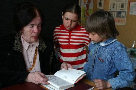 villaggio Podol, regione di Tver, Russia - 2 maggio 2006: insegnante rurale legge ragazze di libri di testo studentesse nella scuola primaria classe.