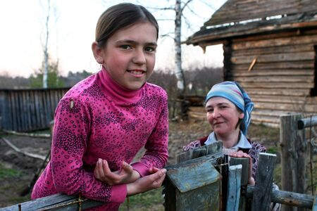 11 years: Lipovec village, Tver region, Russia - May 1, 2006: Peasant girl Tanya 11 years old, standing at the fence near the farmhouse, not far from his mother spring evening.