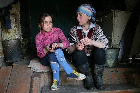 pobreza: Lipovec pueblo, región de Tver, Rusia - 2 de mayo 2006: las mujeres de agricultores se sientan en los pasos de la entrada a la casa de campo. Editorial