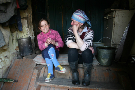 11 years: Lipovec village, Tver region, Russia - May 2, 2006: Mature woman talking with a girl 11 years old sitting on the steps of the farmhouse. Editorial