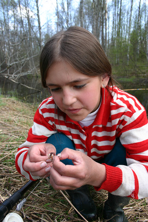 11 years: Lipovec village, Tver region, Russia - May 6, 2006: Rural teenager girl Tanya Shchegolev 11 years old the spring fishing skewer a worm on a hook.