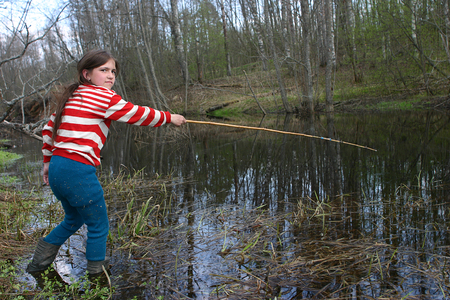 Lipovec village, Tver region, Russia - May 6, 2006: Rural adolescent girl Tanya Shchegoleva 11 years old shod in rubber boots, fishing in a small river using bamboo rods. Editorial