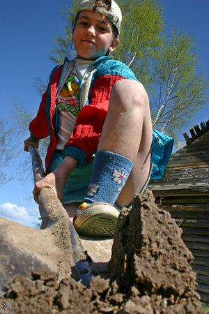 garden settlement: Lipovec village, Tver region, Russia - May 7, 2006: Rural Farmer girl Tanya Shchegolev 11 years old digs up soil in the family garden.
