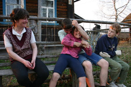 three children: Lipovec village, Tver region, Russia - May 5, 2006: Rural sittings near the wooden house, an adult woman and three children having fun relaxing on a bench. Editorial