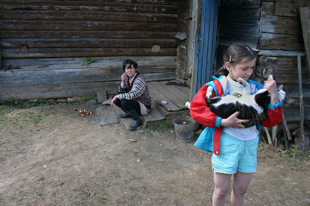 11 years: Lipovec village, Tver region, Russia - May 7, 2006: Tanya Girl 11 years old, standing near a farm house with a cat in her arms, near the porch where her mother was sitting. Editorial