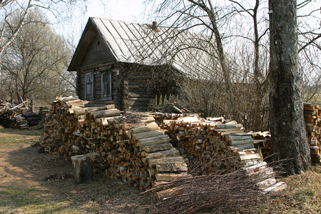 log house: Russian village in the spring, a large stack of firewood near the old log house. Stock Photo