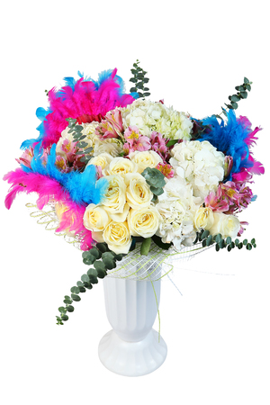 mixed flower bouquet: Floral design with cream roses, white flowers and multicolored painted feathers  in white plastic vase, isolated on white background. Stock Photo