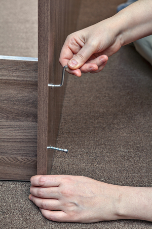 assemblage: Joiner furniture assemblage at home using allen key, hexagonal wrench.