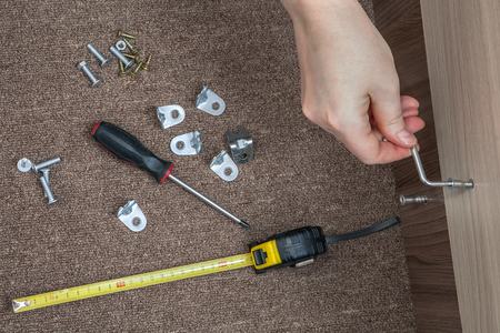 screwed: Assembling wood furniture used Hex wrench, Allen Key, human hand makes screwed furniture screw. Stock Photo