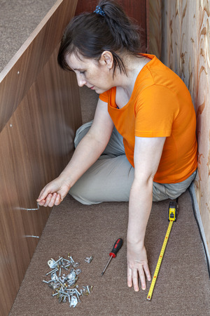 allen key: Assembling of furniture at home, woman housewife collects double bed using the hand tool, hex wrench, allen key.