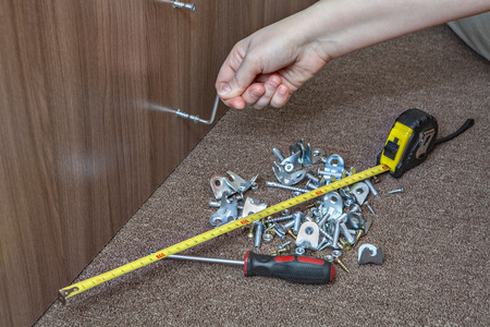 fasteners: Hand tools for assembling furniture, furniture brackets and fasteners, closeup hand tighten the screw using the hex key. Stock Photo