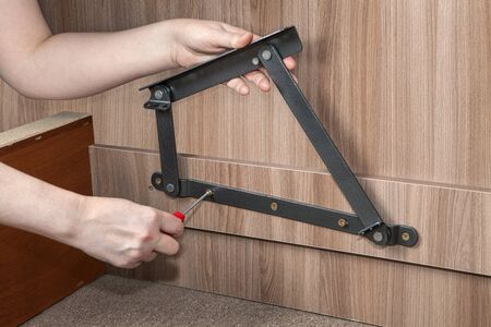 screwed: Assembly folding bedroom wooden furniture, lift up bed frame adjustable metal hinge, close-up hand of carpenter screwed screw using red  phillips-head screwdriver.