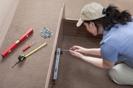 assembler: Self assembling furniture at home, Women putting together self assembly furniture.