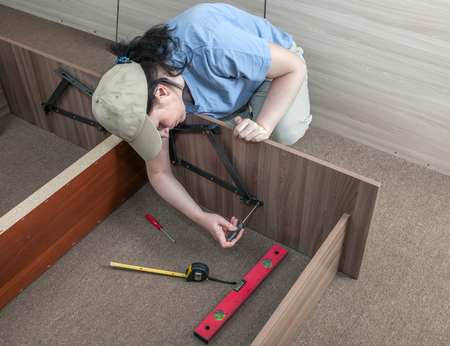 assemble: Self assembling furniture at home, woman housewife putting together assemble bed frame, using hand tools.