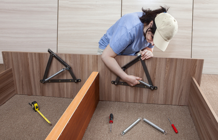 assemble: Self assembling furniture at home, Women putting together self assembly furniture, assemble adjustable lift bed frame spring mechanism system. Stock Photo