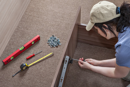 Woman fixes on wooden bed frame folding furniture frame hinge spring lift.