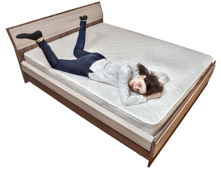 bedstead: One young Caucasian girl is resting on bed innerspring mattress wooden bedstead isolated on white background. Stock Photo