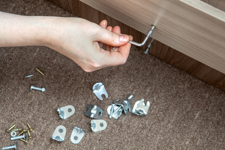 Self-assembly furniture, hand with an Allen key tighten screw. Stock Photo