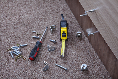 metalware: Metal fittings, clamps and hand tools for installing furniture. Stock Photo