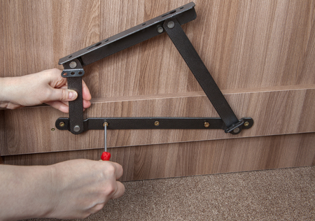 turnscrew: Furniture Installation, Installing steel spring bed lift system, close-up hands of installer furniture tighten screw using a screwdriver.