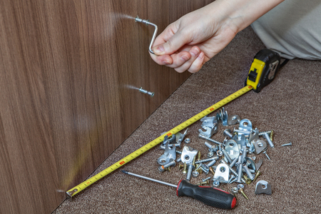 Assembling furniture using allen key, close-up hand turning hex wrench in diy furniture.