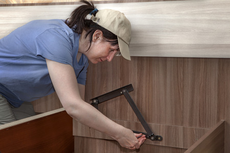 Woman assembles furniture for sleeping, steel hinges lifting mechanism screwed to the frame.