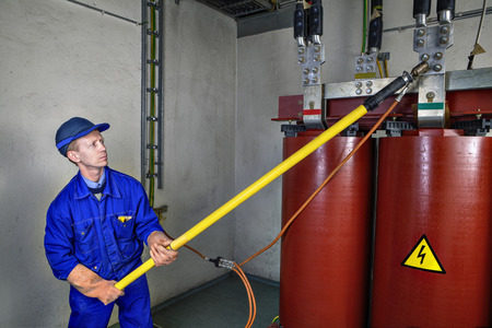 earthing: Electrician Engineer impose temporal earth connection on reducing power transformer, to safety operation of using an insulated rod.