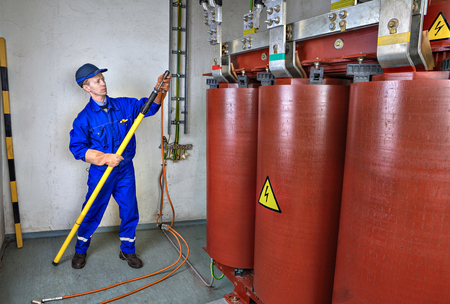 grounding: Electrician impose earth grounding connection on reducing power transformer, using portable earthing insulating stick. Stock Photo