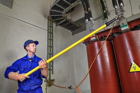ingeniero electrico: Ingeniero el�ctrico impone tierra temporal en la reducci�n de transformador de potencia, para garantizar la seguridad del uso de una varilla aislante.
