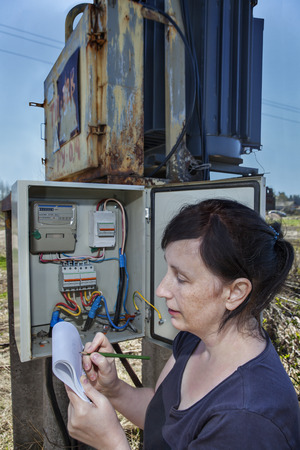 switchgear: Woman electrician engineer inspecting electric counter equipment in distribution fuse box, electricity switchgear  power transformer substation, outdoors.
