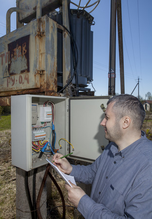 electric meter: Rural transformer substation Electrician Worker Inspecting Electric Meter to check consumption. Stock Photo