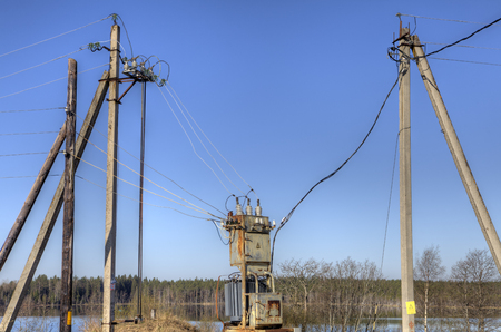 sub station: Electricity supply power lines from local electrical substation, connected to a distribution transformer in the countryside springtime.