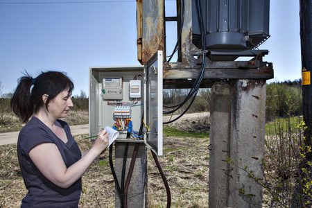 electricity meter: Technician woman checking electricity meter and invoice,  standing near electricity switchgear  power transformer substation, outdoors.